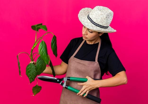 Jovem e linda jardineira de avental e chapéu segurando uma planta e um cortador de cerca viva