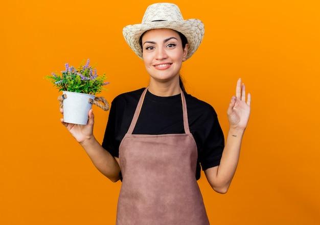 Jovem e linda jardineira de avental e chapéu segurando uma planta em um vaso olhando para a frente, sorrindo, mostrando uma placa de ok em cima da parede laranja