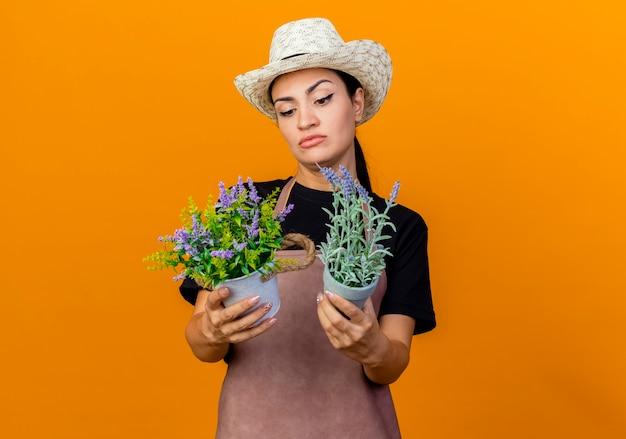 Jovem e linda jardineira de avental e chapéu segurando vasos de plantas olhando para eles confusa em pé sobre a parede laranja