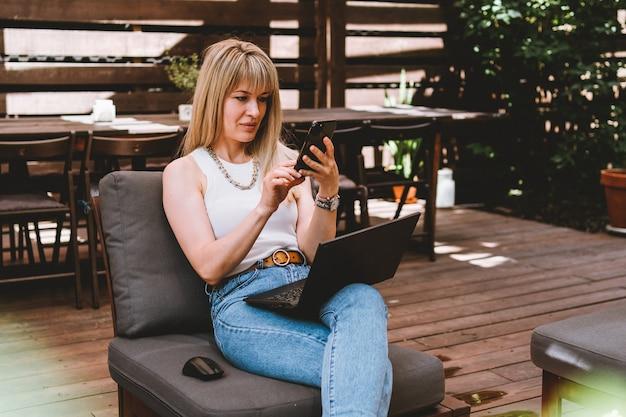 Jovem e linda loira trabalhando em um laptop e falando ao telefone em um aconchegante espaço de coworking