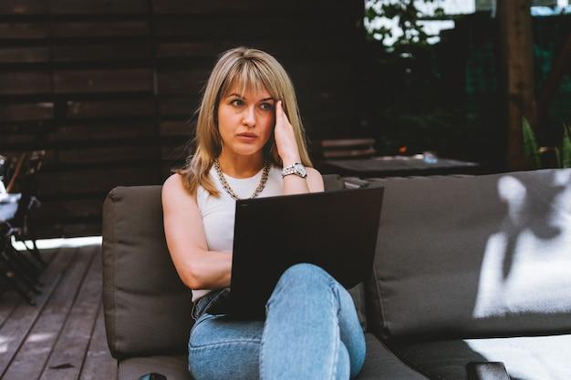 Jovem e linda loira trabalhando em um laptop em um espaço de coworking aconchegante