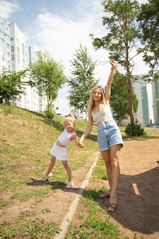 Jovem e linda mãe com a filha no quintal de verão