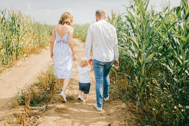 Jovem e linda mãe, forte pai caucasiano brincando com seu filho loiro bonito em um milharal.