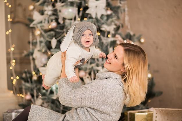 Jovem e linda mãe loira posando com seu filho em um fundo de natal
