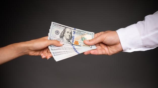 Jovem e linda mão feminina dá um monte de dinheiro para a mão masculina de um empresário por serviços