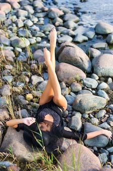 Jovem e linda modelo de biquíni deitada em uma praia rochosa