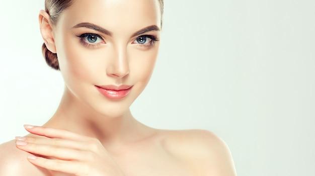 Jovem e linda modelo está tocando suavemente sua própria pele perfeitamente cuidada.