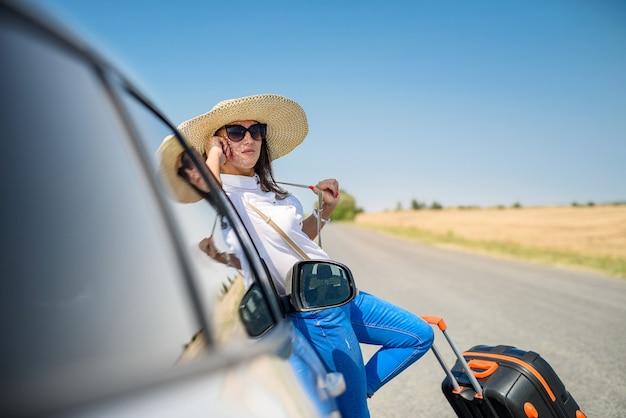 Jovem e linda modelo feliz perto do carro em uma viagem de verão