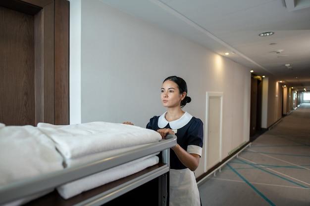 Jovem e linda morena camareira ou trabalhadora de hotel empurrando carrinho com toalhas limpas dobradas e outras coisas enquanto se move pelo corredor