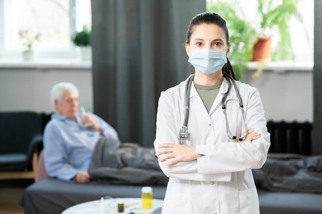 Jovem e linda morena médica em jaleco branco e máscara protetora, cruzando os braços sobre o peito e olhando para você contra paciente idoso doente na cama