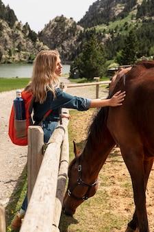 Jovem e linda mulher acariciando um cavalo