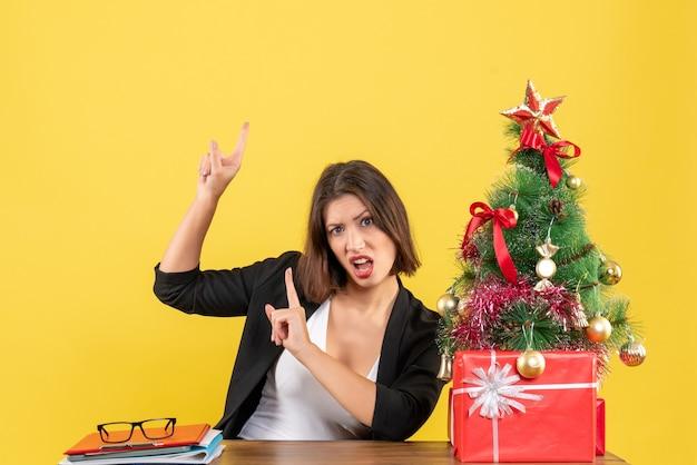 Jovem e linda mulher apontando para cima surpreendentemente sentada em uma mesa perto da árvore de natal decorada no escritório em amarelo
