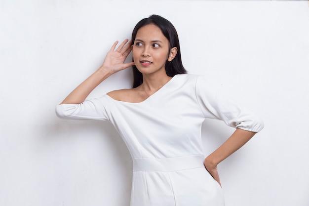 Jovem e linda mulher asiática com a mão na orelha ouvindo uma audiência de fofoca isolada no branco