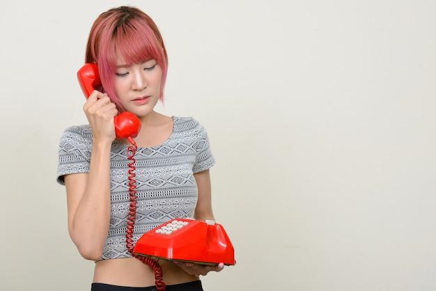 Jovem e linda mulher asiática com cabelo rosa contra uma parede branca