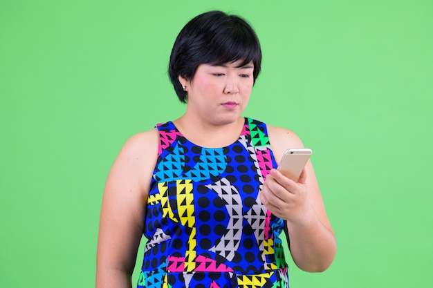 Jovem e linda mulher asiática com excesso de peso pronta para a festa contra chroma key com parede verde