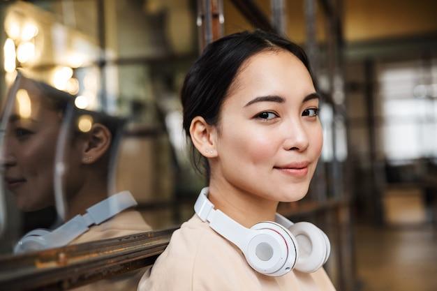 Jovem e linda mulher asiática com fones de ouvido sorrindo enquanto trabalhava no escritório