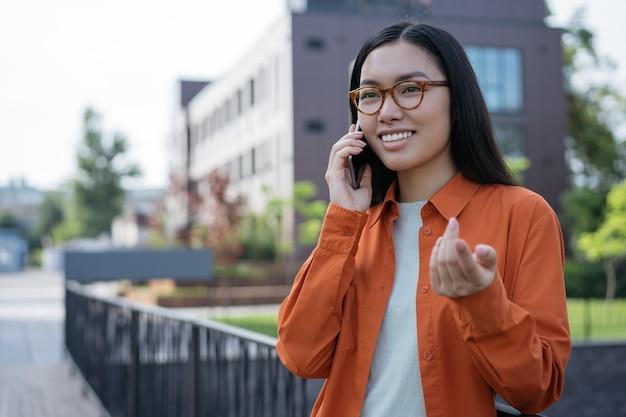 Jovem e linda mulher asiática falando no celular, discutindo algo na rua