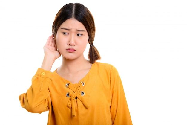 Jovem e linda mulher asiática ouvindo