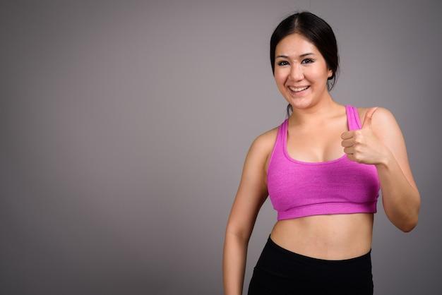 Jovem e linda mulher asiática pronta para a academia contra uma parede cinza