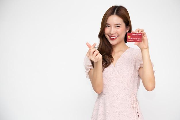 Jovem e linda mulher asiática sorrindo, segurando um cartão de crédito isolado na parede branca
