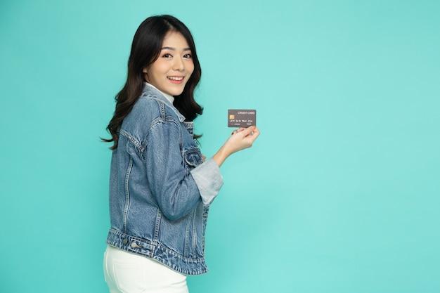 Jovem e linda mulher asiática sorrindo, segurando um cartão de crédito isolado no fundo verde