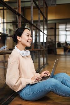 Jovem e linda mulher asiática trabalhando em um laptop enquanto está sentada no chão de um escritório