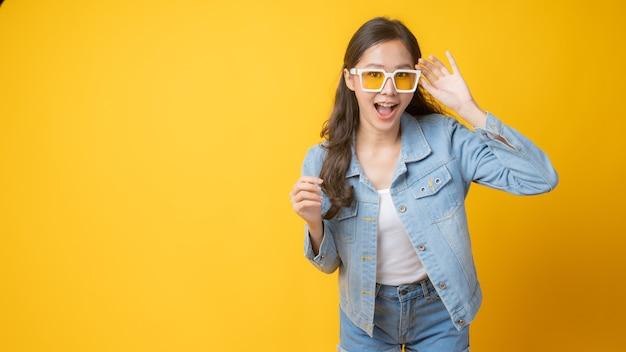 Jovem e linda mulher asiática usando óculos escuros amarelos em jeans, posando e sorrindo