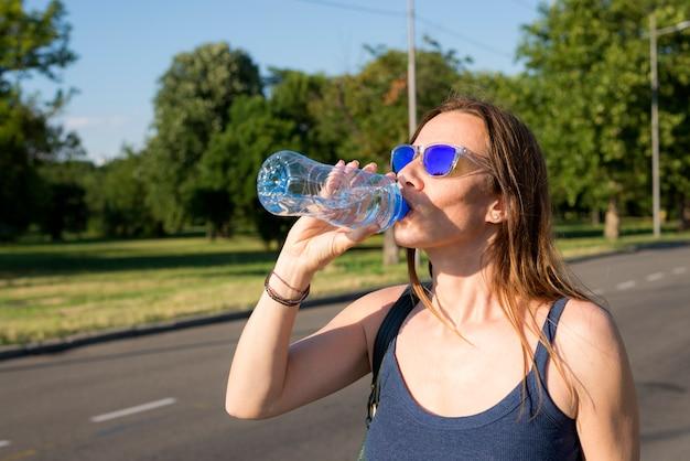 Jovem e linda mulher bebendo garrafa de água