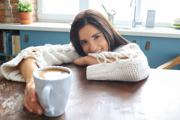 Jovem e linda mulher bebendo uma bebida quente na cozinha
