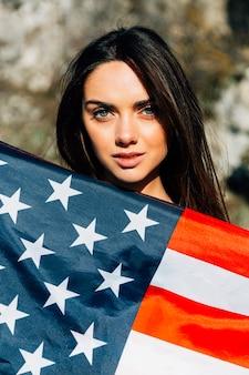 Jovem e linda mulher coberta com a bandeira americana