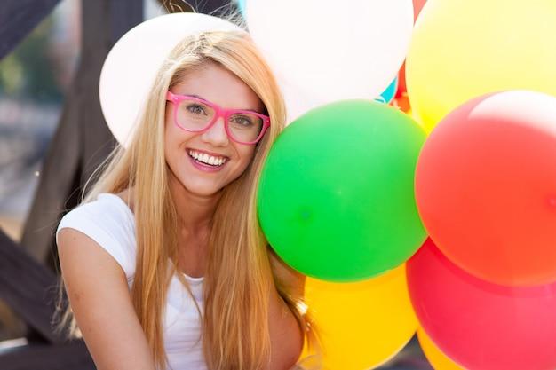 Jovem e linda mulher com balões de ar