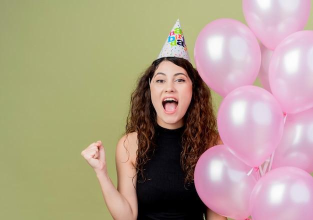 Jovem e linda mulher com cabelo encaracolado em um boné de férias segurando balões de ar cerrando o punho cerrando o conceito de festa louca feliz aniversário sobre a luz
