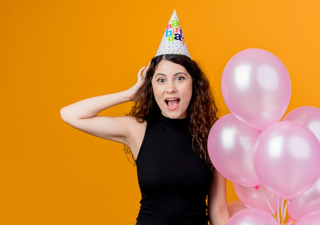Jovem e linda mulher com cabelo encaracolado em um boné de férias segurando balões de ar surpresa e feliz aniversário conceito de festa em pé sobre a parede laranja