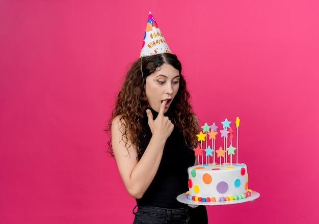 Jovem e linda mulher com cabelo encaracolado em um boné de férias segurando um bolo de aniversário olhando para ele surpreso e surpreso com o conceito de festa de aniversário em pé sobre a parede rosa