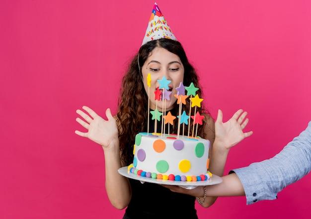 Jovem e linda mulher com cabelo encaracolado em um boné de férias segurando um bolo de aniversário, olhando para um bolo de aniversário surpreso e feliz aniversário conceito de festa rosa