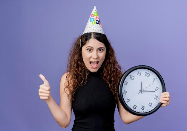 Jovem e linda mulher com cabelo encaracolado em um boné de férias segurando um relógio de parede e sorrindo alegremente mostrando os polegares para cima do conceito de festa de aniversário em pé sobre a parede azul