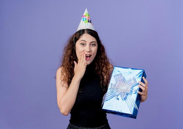 Jovem e linda mulher com cabelo encaracolado em um boné de férias segurando uma caixa de presente de aniversário e parecendo espantada com o conceito de festa de aniversário em pé sobre a parede azul