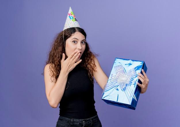 Jovem e linda mulher com cabelo encaracolado em um boné de férias segurando uma caixa de presente de aniversário, parecendo surpresa com o conceito de festa de aniversário em pé sobre a parede azul