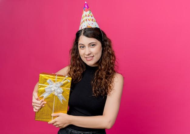 Jovem e linda mulher com cabelo encaracolado em um boné de férias segurando uma caixa de presente de aniversário sorrindo alegremente conceito de festa de aniversário rosa