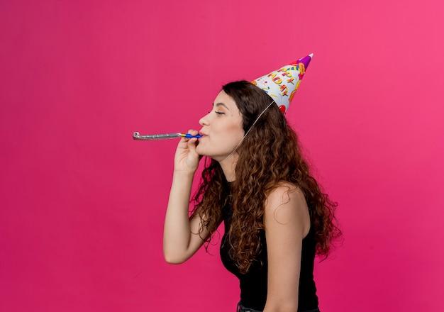 Jovem e linda mulher com cabelo encaracolado em um boné de férias soprando apito conceito de festa de aniversário em pé sobre a parede rosa