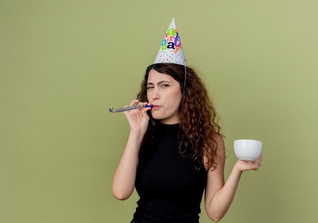 Jovem e linda mulher com cabelo encaracolado em um boné de férias, soprando apito segurando a xícara de café, parecendo displicente com o conceito de festa de aniversário sobre a luz