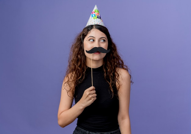 Jovem e linda mulher com cabelo encaracolado na tampa do feriado segurando bigodes de festa em pé sobre a parede azul