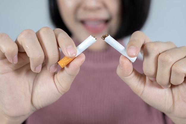 Jovem e linda mulher com cigarro quebrado