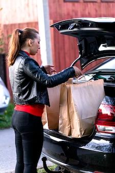 Jovem e linda mulher com compras no supermercado, colocando sacos de papel no porta-malas aberto