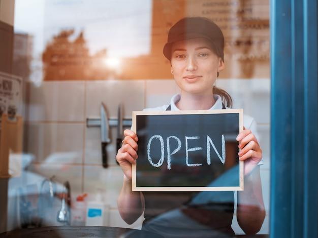 Jovem e linda mulher com um avental, um trabalhador de café segura uma placa aberta contra o fundo de um bistrô atrás da janela de vidro