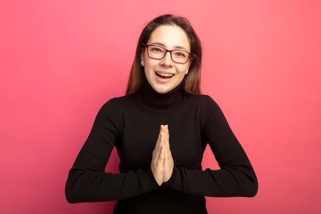 Jovem e linda mulher com uma gola alta preta e óculos de mãos dadas como se estivesse orando feliz e animada em pé sobre uma parede rosa