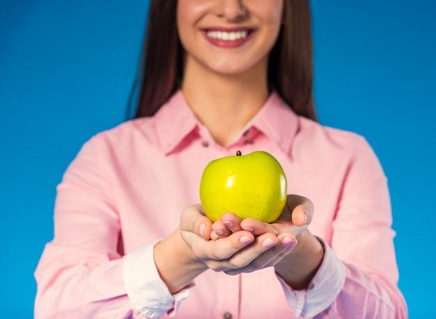Jovem e linda mulher com uma maçã verde.
