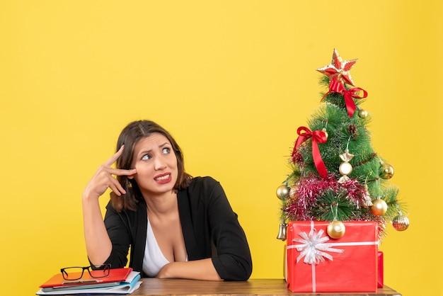 Jovem e linda mulher confusa sobre algo surpreendentemente sentado em uma mesa perto da árvore de natal decorada no escritório em amarelo