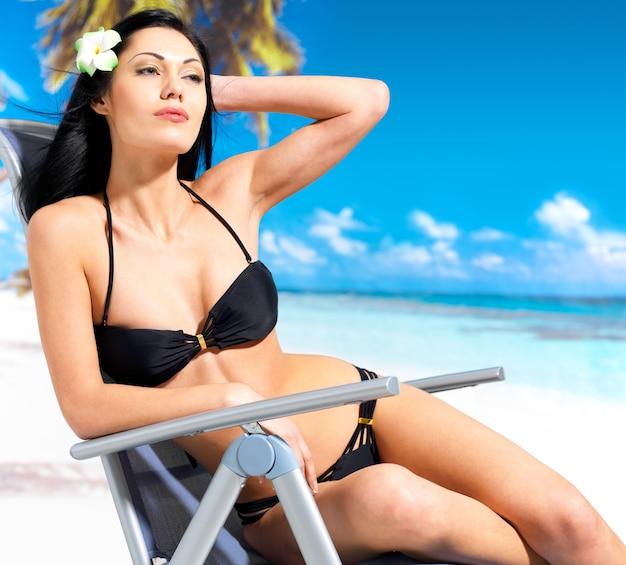 Jovem e linda mulher curtindo na praia, sentada na cadeira