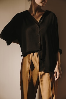 Jovem e linda mulher de camisa preta e calça marrom encostada na parede